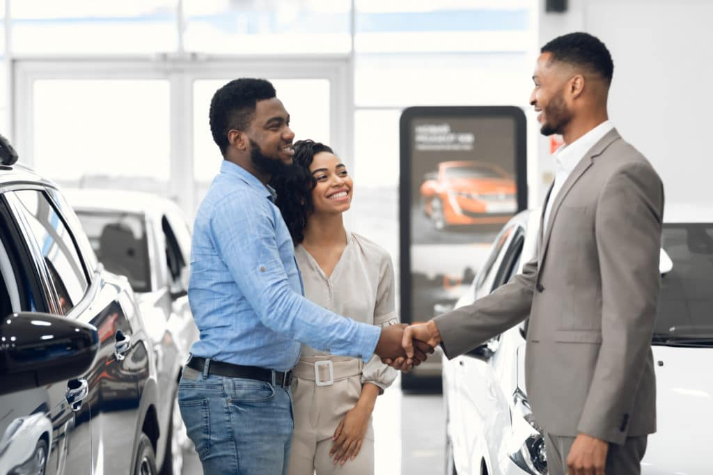 Car Dealer Handshaking With Happy Auto Buyers After Successful Deal In Dealership Store.