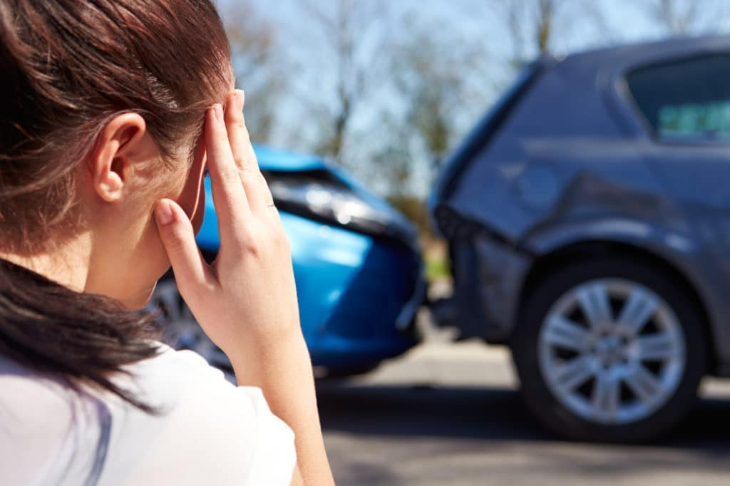 Distressed woman looking at car accident