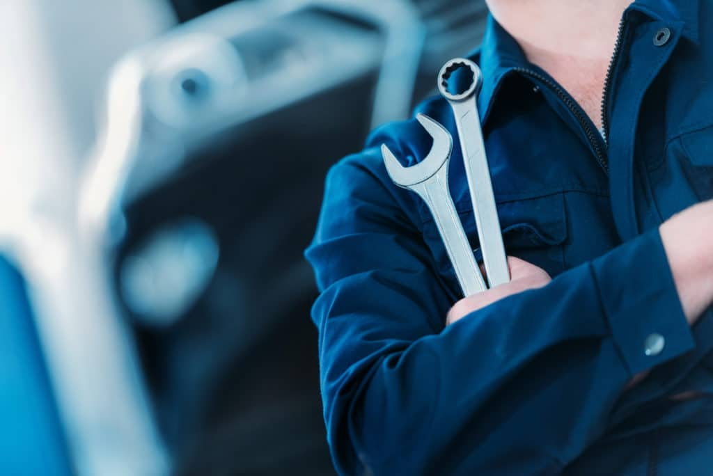closeup of mechanic holding combination wrenches